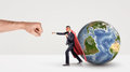 A small businessman in a red cape and a mask punching a giant fist with a small earth sphere behind him.