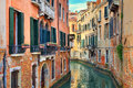 Small canal among old houses. Venice, Italy. Royalty Free Stock Images