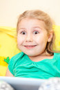 Small caucasian girl funny smile wide opened eyes sitting tablet pad Royalty Free Stock Photos