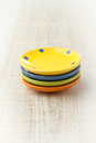 Small ceramic plates pile of colorful on white wooden board Stock Image