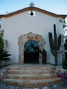 Small chapel recently renovated in cabo mexico san jose del baja glass door cactus and a bell Stock Image
