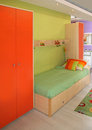 Small child bedroom with modern green and orange furniture Stock Images