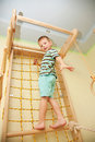 Small child climbing on a rope net bottom view playing sports at sport center kid Stock Photos