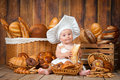 Small child cooks a croissant in the background of baskets with rolls and bread. Royalty Free Stock Photo