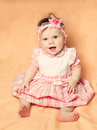 Small child half year old on a soft pastel background little girl in dress sitting Royalty Free Stock Images