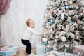 Small child hangs Christmas balls on the  tree Royalty Free Stock Photo