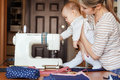 Small child learns new knowledge, along with his mother inspects sewing machine. Work at home, parenting, parents and