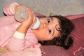 Small child lying and drinking milk product from bottle Royalty Free Stock Photo