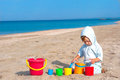 Small child play on the beach with different size toy bucket Royalty Free Stock Photo