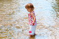 Small child play on the shallow water in bright clothes Royalty Free Stock Photos