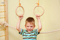 Small child playing sports at sport center kid exercising on gymnastic rings Royalty Free Stock Images