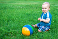 Small child the plays on a green summer meadow Royalty Free Stock Photos