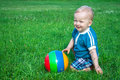 Small child the plays on a green summer meadow Royalty Free Stock Images