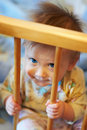Small child sits in his wooden bed Stock Photography