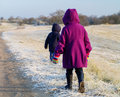 Small children in frosty landscape duffel coats and winter clothing walking into a dune Royalty Free Stock Image