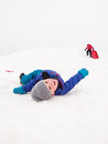 Small children sledging boy lying smiling on snow at teh bottom of a hill Stock Photography