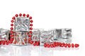 Small Christmas gifts in shiny silver paper and red tinsel beads ornament Royalty Free Stock Photo