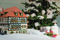 Small Christmas house near the Christmas tree with decorations Royalty Free Stock Photo