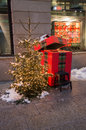 Small christmas tree snow covered in a square of zurich with a gift box behind Royalty Free Stock Photos