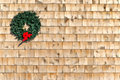 Small christmas wreath on a cedar shingle wall holiday with red ribbon Royalty Free Stock Image