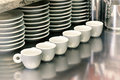 Small coffee cups on a metal cafeteria counter Royalty Free Stock Photo