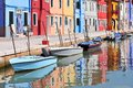 Small colored houses and the boats in sunny summer day, Venice Burano island, Italy.