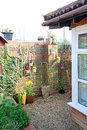 Small cottage courtyard garden photo of a kent country showing various potted flowers and plants and hanging baskets Royalty Free Stock Photo