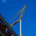 Small crane and wall against the blue sky building tower background of Royalty Free Stock Photos