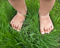 Small cute baby feet on the green grass Royalty Free Stock Photo