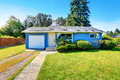 Small cute blue house with driveway and trimmed hedges northwest usa Stock Photo