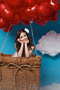 Small cute girl flying on red heart balloons Valentines day Royalty Free Stock Photo