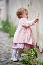 Small cute girl standing near old wall Stock Photography
