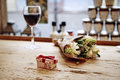 Small cute present box with bow at wooden table, flowers and glass of wine behind. Romantic meeting in cafe. St. Valentine`s day c Royalty Free Stock Photo