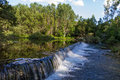 Small dam on the river and waterfall in channel to divert water for irrigation Stock Image