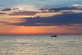Small fishing boat over seacoast skyline with sunset background Royalty Free Stock Photo