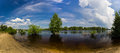 Small flood flooding trees stand in the water set of footprints on the sandy shore the dnieper river near kiev ukraine Stock Photo
