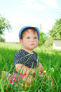 Small funny girl sitting in the grass summer bright sunny day little little garden Royalty Free Stock Image