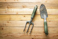 Small gardening shovel and fork on wooden background Royalty Free Stock Photo