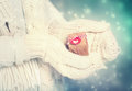 Small gift box in womans hands with white gloves handmade the snowing night Stock Images
