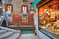 Small gift shop illuminated showcase near bridge over narrow canal against red brick wall evening venice italy Royalty Free Stock Image