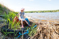 Small girl on the bank of river with rubbish wioth near Stock Image
