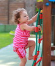 Small girl child climbing up on children activity ladder outdoors Stock Photos