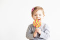 Small girl eating lollipop. Happy children with a big delicious Royalty Free Stock Photo