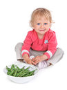Small girl with grean peas Stock Photos