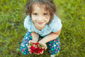 Small girl with a handful of strawberries Royalty Free Stock Photo