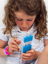 Small girl loom banding close up of wearing a band bracelet stretching elastic bands onto a band Royalty Free Stock Photos