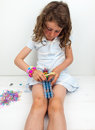 Small girl loom banding in summer dress wearing band bracelets Royalty Free Stock Image