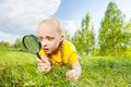 Small girl with magnifier looking through glass found something and while laying on the green grass during beautiful summer day in Royalty Free Stock Image