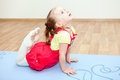 Small girl making yoga pose on mat in gym Royalty Free Stock Photo