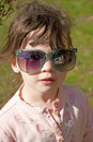 Small girl modeling big sunglasses. Stock Image